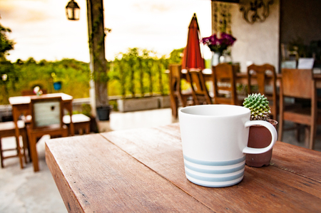Cup of morning coffee on a wooden table under the morning sun 写真素材