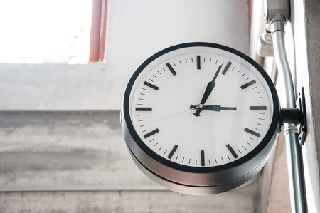 Standard clock hanging from the concrete wall