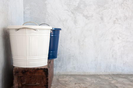Multi purpose blue and white metal bucket sitting on a wooden chest Imagens