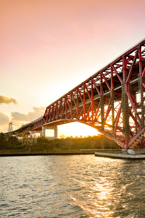 Sunset at the Minato Bridge (red bridge) in Osaka cross over Osaka sea port Stock Photo