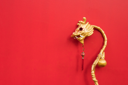 Golden Chinese style decorated dragon wand on red background 写真素材