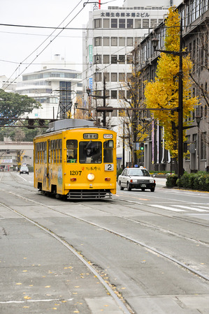 Kumamoto, Japan -December 15, 2009: Classic yellow tram of Kumamoto city with yellow ginko leaves background
