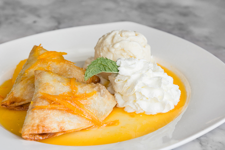 Crepes Suzette: French thin pancake with orange sauce and ice cream