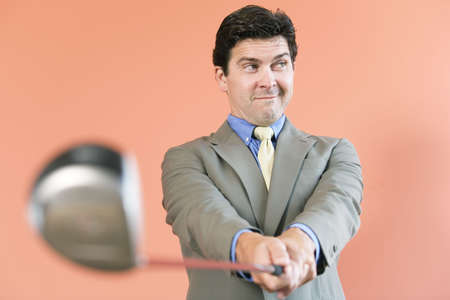 indoor shot: View of a business man with a golf club. Stock Photo