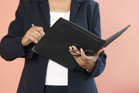 Midsection of a business woman writing in a file. photo