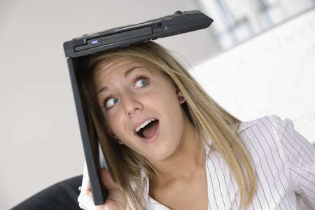 fair skin: Una mujer de negocios con una computadora port�til sobre su cabeza.  Foto de archivo