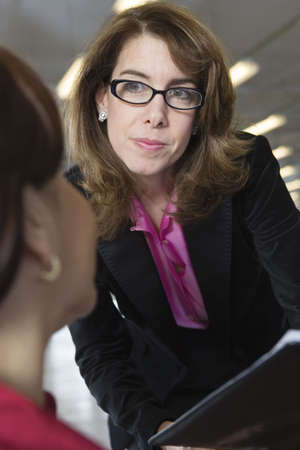 verticals: View of two business women in a discussion.