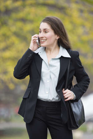 blissfulness: View of a business woman talking on the phone and smiling.