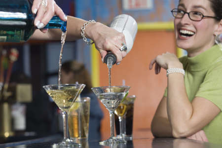 blissfulness: View of a young woman laughing at the bar counter.