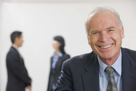 Portrait of smiling executive with co-workers out of focus in the background. Stock Photo