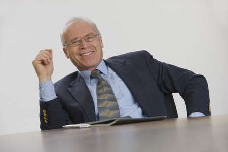 Executive relaxed and smiling from his conference table seat.