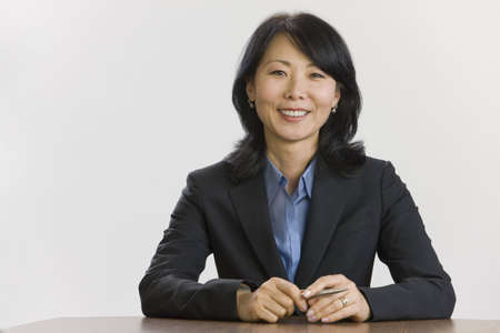 Portrait of Asian businesswoman seated at table. Stock Photo