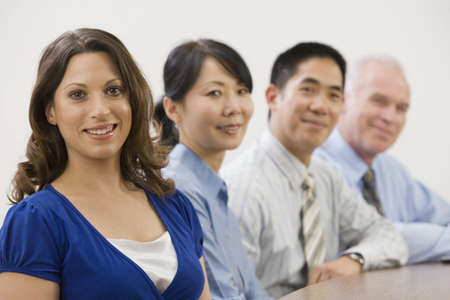 Line of four smiling businesspeople sitting in a meeting at a conference table.  Multi-ethnic diversity.