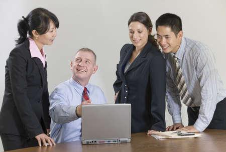 laptop: Mature businessman showing laptop display to team.
