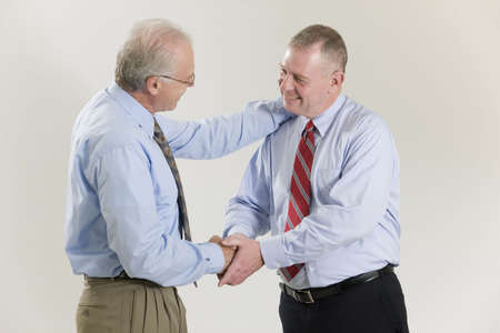 Businessman congratulating and shaking hand of colleague after success. LANG_EVOIMAGES