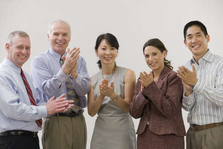 Business team clapping hands over success.  Standing lined up.  Five member team with diversity in age, gender and ethnicity.  Shirt and ties in informal seting.  White background for copyspace.