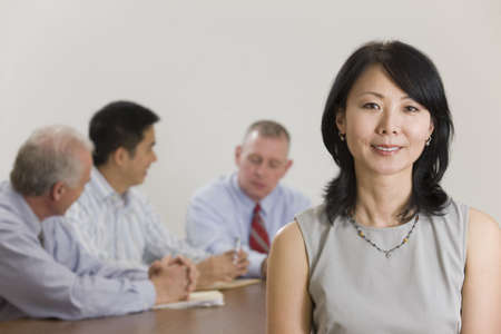 Portrait of woman executive standing in front of her team