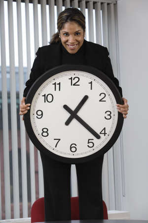elapsed: Portrait of a business woman standing on an office chair in a meeting and showing the deadline using a wall clock for emphasis.