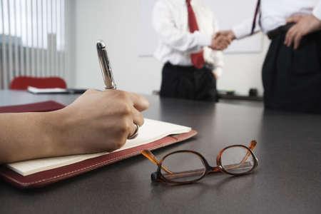 persona escribiendo: Persona escribir con hombres de negocios, agitando las manos en el fondo.