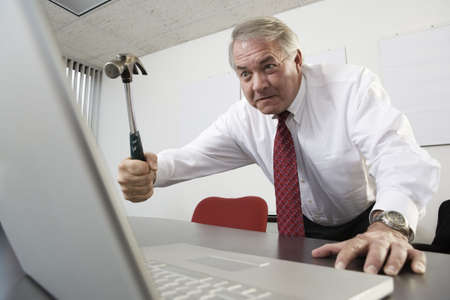 View of a business man trying to hit a laptop with a hammer.