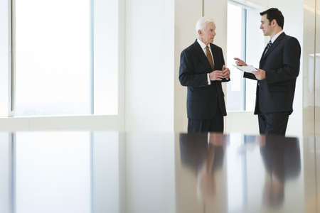 management meeting: Two businessmen in focus in the background near bright windows of a conference room .