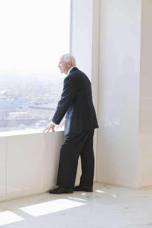window view: View of a senior businessman standing at an office window looking out into the distant cityscape.