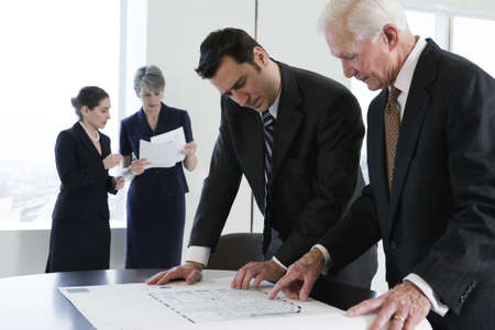View of two businessmen reviewing office layout plans in a conference room with a city view in background.  Two businesswomen in background discussing paperwork.