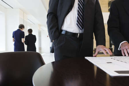 View of four businesspeople reviewing corporate plans in an office conference room.