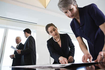 View of businesspeople planning in an office.  Two businesswomen in foreground reviewing plans.  Waist up view.  Senior executive discussing paperwork with colleague in background.