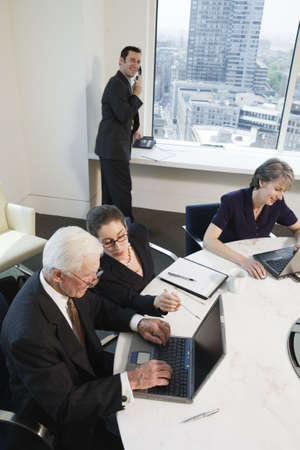 Four businesspeople meeting with laptops in a conference room with a city view. Stock Photo - 5579450