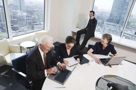 書類上のラップトップ上のオフィスで働く 4 つのビジネスマンのビュー。