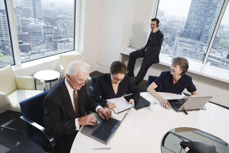 View of four businesspeople working in an office over laptops on paperwork. LANG_EVOIMAGES