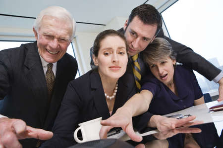 View of four businesspeople in an office reaching for the telephone. Stock Photo - 5579455