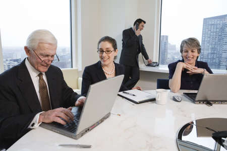 View of businesspeople working in an office conference room with laptops.