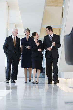 View of four businesspeople walking in a corridor deep in conversation.