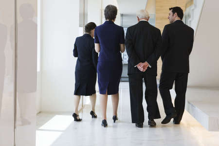 Four businesspeople walking in a corridor discussing plans and strategy.