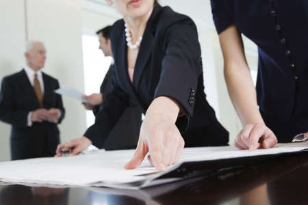View of four businesspeople discussing plans in an office.  Cropped close up of two businesswomen in foreground pointing at plans.  Two businessmen in bacground discussing paperwork.