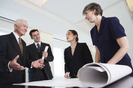 reviewing: View of businesspeople discussing a contract and plans in an office meeting. LANG_EVOIMAGES