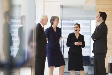 View of businesspeople smiling and conversing while standing in an office. LANG_EVOIMAGES