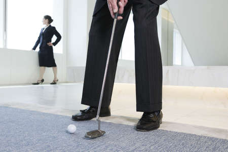 View of businessman playing golf with woman standing in background.