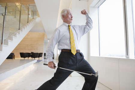 上げられた握りこぶしでゴルフ クラブ ジェスチャー successs とオフィスのロビーに立っている興奮しているビジネスマンのビュー。