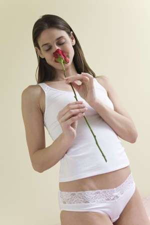 A beautiful young woman in lingerie smelling a rose. Stock Photo - 5604137