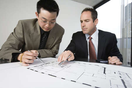 Two architects discussing on blueprints in an office. Stock Photo