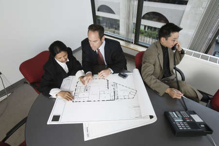 asian architect: View of businesspeople checking blueprint with an architect speaking on phone. Stock Photo
