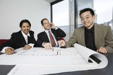 architect: Portrait of businesspeople smiling in an office meeting. Stock Photo