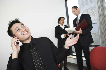 View of architect talking on moblie phone with businesswoman and manager discussing in background. Stock Photo - 5593523