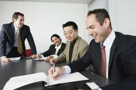 iew of four businesspeople in an office meeting. Stock Photo