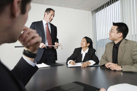 View of four businesspeople in an office meeting. Stock Photo