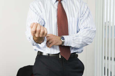 unknown age: View of a businessman rolling up sleeves.