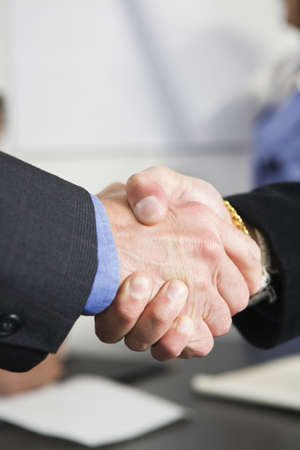 View of businessmen shaking hands in an office. photo